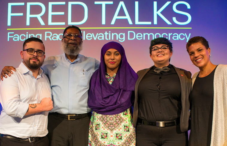 5 people with arms on each other's shoulders under the title FRED Talks (Facing Race Elevating Democracy)